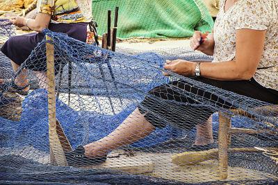 Mujeres obreros trabajando reparando redes de pesca en un puerto